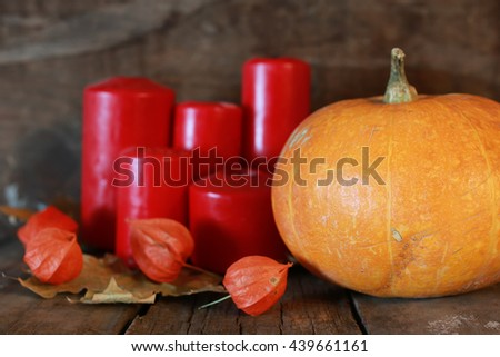 pumpkin and candle on old wooden - stock photo