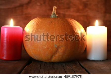 pumpkin and candle on old wooden