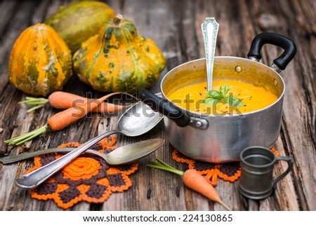 Pumpkin and carrot soup in the old stainless casserole pan - stock photo