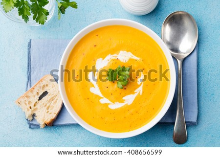 Pumpkin and carrot soup with cream and parsley on blue stone background Top view - stock photo