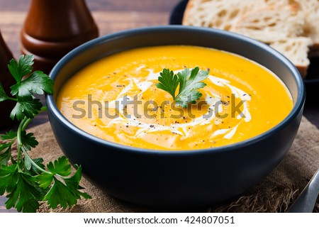 Pumpkin and carrot soup with cream and parsley on dark wooden background - stock photo