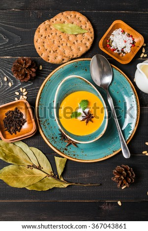 Pumpkin and carrot soup with cream and seasoning in blue bowl  on black wooden background, top view - stock photo