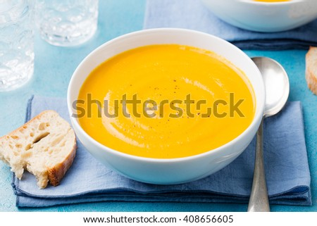 Pumpkin and carrot soup with cream on blue stone background  - stock photo