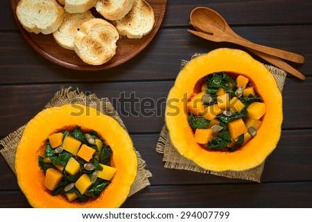 Pumpkin and chard salad with roasted pumpkin seeds served in pumpkin halves with toasted bread on the side, photographed overhead on dark wood with natural light   - stock photo