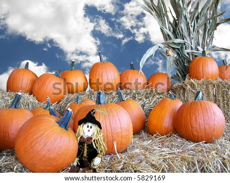 pumpkin and scarecrow on bales - stock photo
