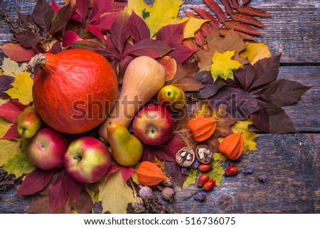 Pumpkin, apples, nuts, pears, physalis and autumn leaves on a wooden background old. Top view.
