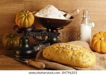 Pumpkin bread in farmhouse setting with flour and milk