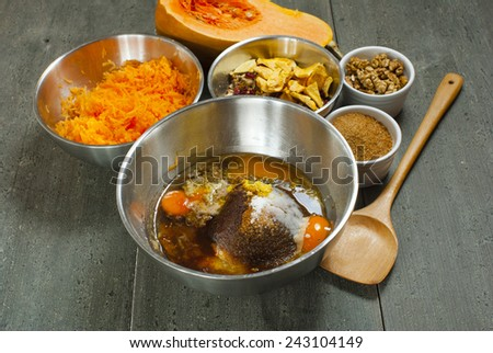 pumpkin bread ingredients in alloy mixing bowls, aged wood table background - stock photo