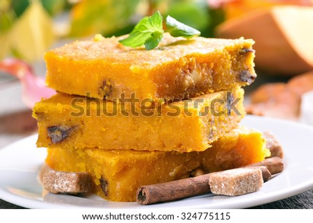 Pumpkin cake with nuts on wooden table, close up view