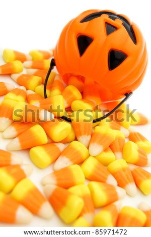 Pumpkin candy holder with spilling Halloween candy corn on a white background - stock photo