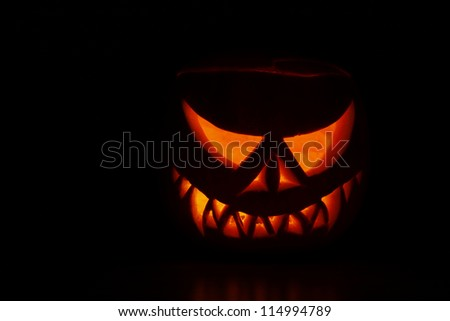 Pumpkin carved into spooky demon face for haloween - stock photo