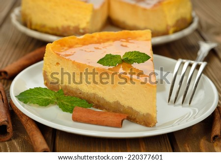 Pumpkin cheesecake with caramel icing on brown background - stock photo
