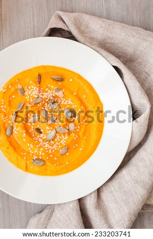 Pumpkin cream-soup with chili and seeds in a white plate - stock photo
