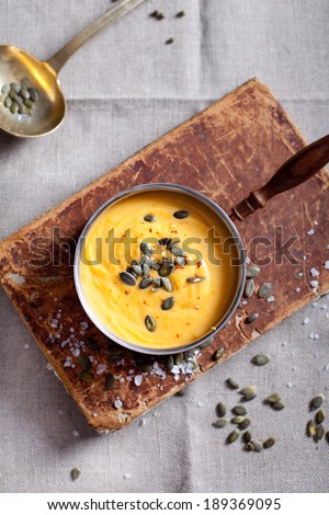 Pumpkin cream soup with pumpkin seeds in a vintage cooper roasting pan on a vintage book and textile canvas background - stock photo