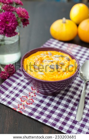 Pumpkin cream-soup with seeds in a plate on the wooden table - stock photo
