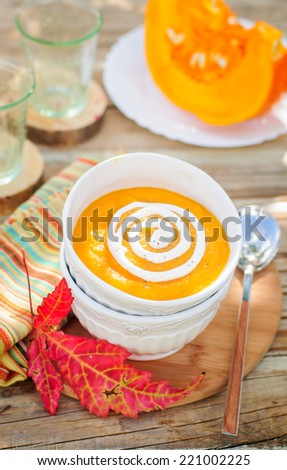 Pumpkin Cream Soup with Sour Cream in a White Bowl, copy space for your text, shallow dof