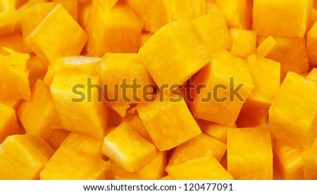 Pumpkin cut in small square blocks background - stock photo