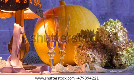 Pumpkin, glass cups, hydrangea and lamp warm light. Romantic lace and delicate purple ribbon. Still for evening, Halloween, holiday, Thanksgiving and autumn weddings.