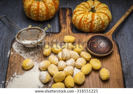 pumpkin gnocchi Ingredients for cooking strainer spoon flour on ?utting board on dark rustic background  close up - stock photo
