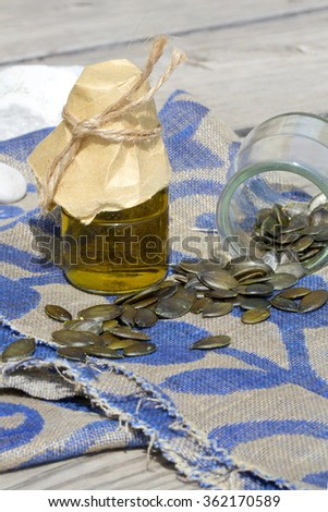 Pumpkin green seeds oil in a glass bottle on a decorative sackcloth - stock photo