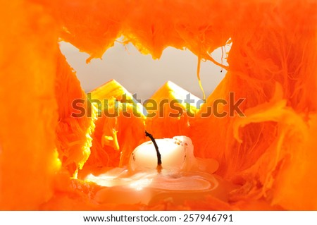 Pumpkin interior with melted candle illuminated with sunlight through the cut hole - stock photo