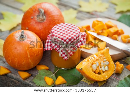 Pumpkin jam, puree or sauce and ripe pumpkins on old wooden table. Autumn still life. Selective focus. - stock photo