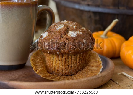 Pumpkin muffin and coffee cup on a wooden plate