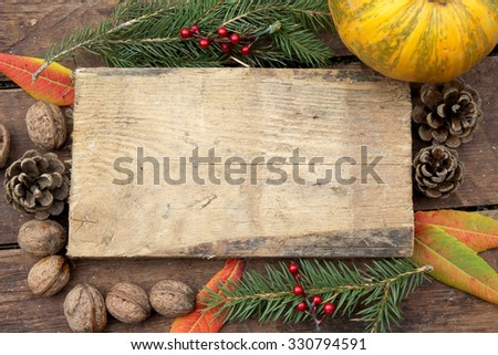 Pumpkin on wooden background - Halloween, Christmas and Thanksgiving concept border - frame - wallnut, pinecone, fir tree, berry and leaves decoration - copy space - stock photo