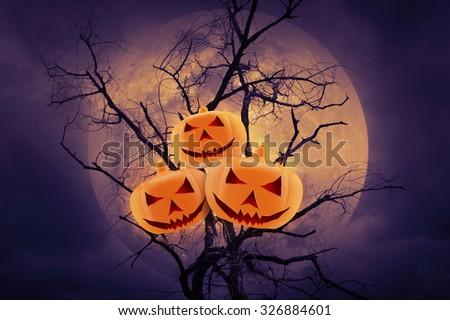Pumpkin over dead tree against full moon, Halloween background - stock photo