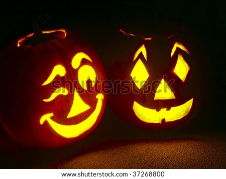 Pumpkin Pair glowing bright with one winking - stock photo