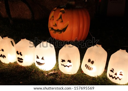 Pumpkin patch with recycled milk jars as ghosts - stock photo
