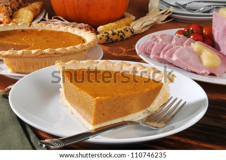 Pumpkin pie, baked ham, cheese and crackers on a festive Thanksgiving dinner table - stock photo