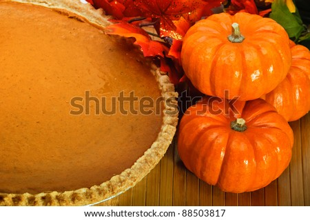 Pumpkin pie in a pie plate with autumn leaves and pumpkins. - stock photo
