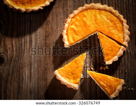 Pumpkin pie on a rustic wooden table - top view