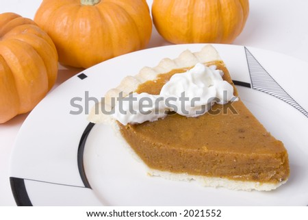 Pumpkin pie on fancy plate and pumpkins in background