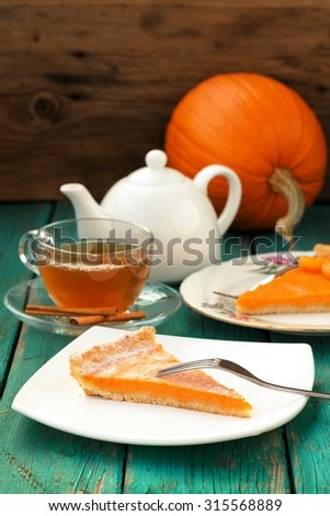 Pumpkin pie, tea in glass cup, white teapot and fresh pumpkin on turquoise table - stock photo