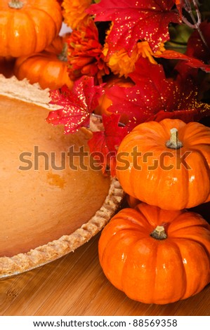 Pumpkin pie with autumn leaves and pumpkins.