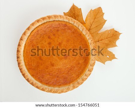 Pumpkin pie with autumn leaves decor - stock photo