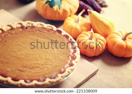 Pumpkin pie with autumn pumpkins and corn on wooden board - stock photo