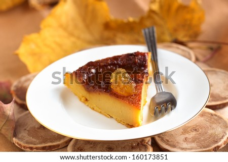 Pumpkin pie with caramel decorated with jam on white plate in natural wood background. - stock photo