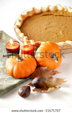 pumpkin pie with chestnuts, pumpkins and candles - stock photo