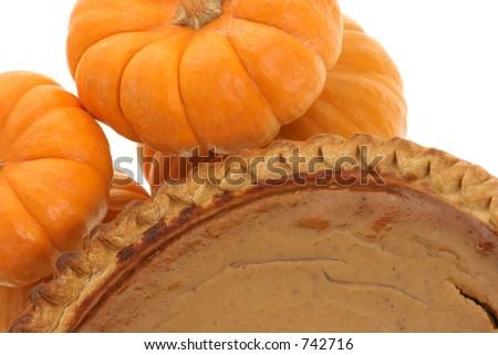 pumpkin pie with pumpkins next to it - stock photo