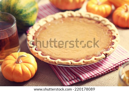 Pumpkin pie with small pumpkins on red striped napkin - stock photo