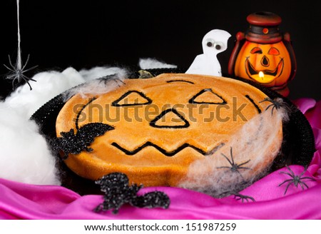 Pumpkin pie with spiders on black background