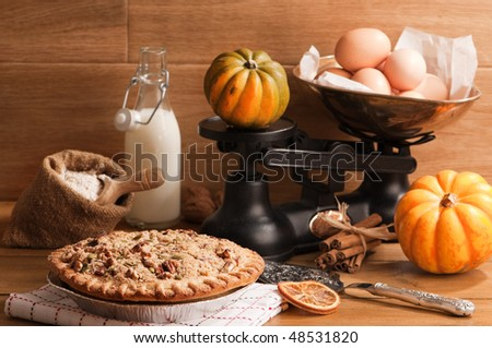 Pumpkin pie with weighing scales and baking ingredients - stock photo
