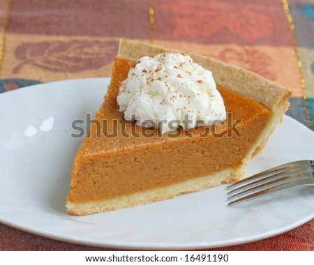 pumpkin pie with whipped cream served on white plate - stock photo