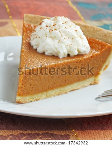 pumpkin pie with whipped cream served on white plate.shallow depth of field with focus on the tip of the pie. - stock photo