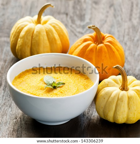 Pumpkin porridge and pumpkins on black wooden table. - stock photo