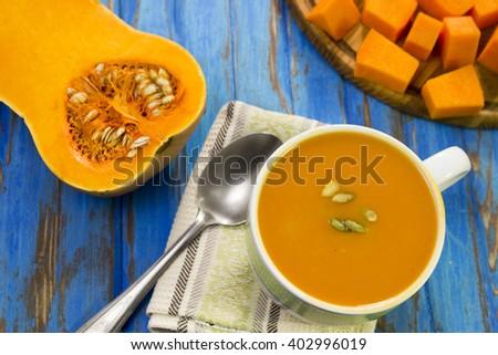 Pumpkin puree soup, some raw pumpkin, pumpkin slices, spoon, blue table. - stock photo