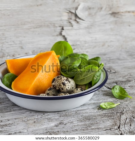 Pumpkin, quail eggs, spinach in the enameled bowl - raw ingredients for cooking, on a light rustic wood table. Healthy food - stock photo